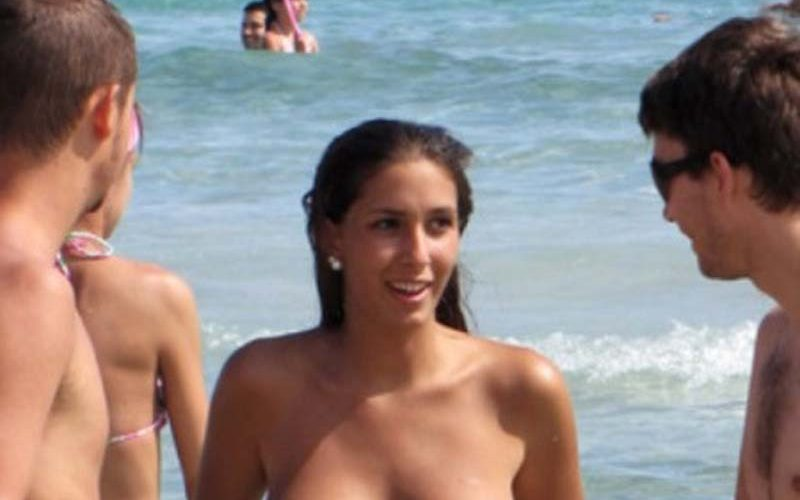 Topless brunette flaunts her perfect tits at the beach