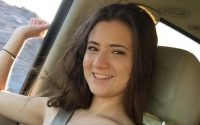Girl topless and smiling in the passenger seat